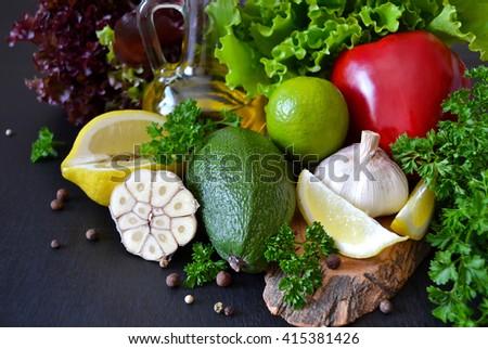 Fresh ripe vegetables, olive oil, lettuce on a black background - stock photo