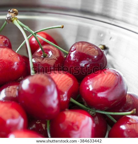 Fresh ripe wet red cherries in a steel plate. Extreme close-up. - stock photo