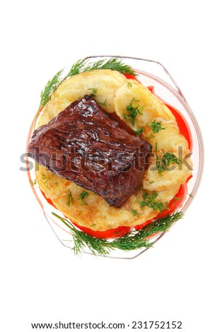 fresh roast beef meat chunk in transparent bowl over baked potatoes and tomatoes served with fill isolated over white background - stock photo