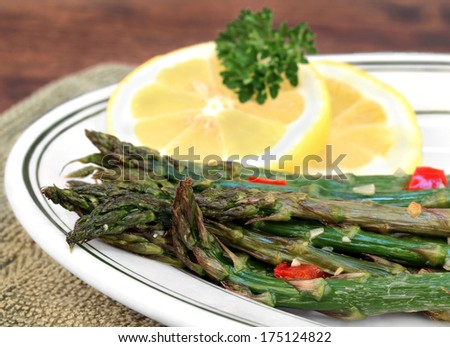 Fresh roasted asparagus with garlic and roasted red pepper.  Macro with selective focus. - stock photo