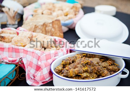 Fresh roasted bread and mutton kebabs in dishes on a table - stock photo