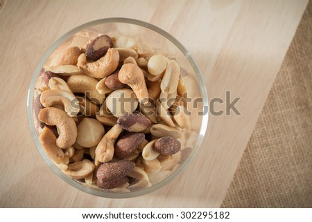 fresh roasted cocktail nuts (many type of nuts) on wooden plate - stock photo