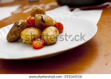 Fresh roasted potato with cherry on white dish - stock photo