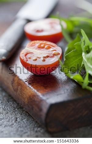 fresh rocket and tomatoes on a wooden chopping board - stock photo