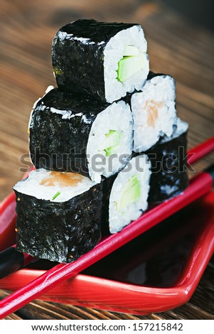fresh roll served in a red plate with black stripes. Focus on the top of the roll. - stock photo
