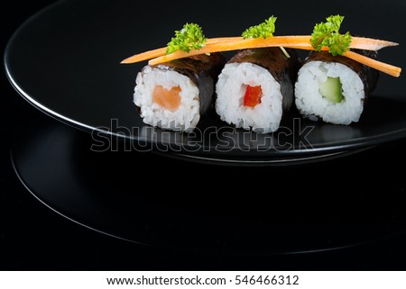 Fresh rolls on a plate, roll with salmon, cucumber and pepper served with carrot slices and parsley, black background