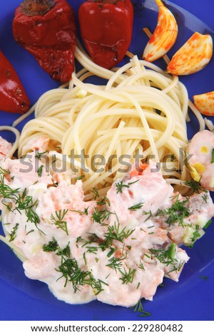 fresh rose wild salmon baked in cream cheese sauce with italian pasta and red hot pepper on blue plate isolated over white background high resolution hidef - stock photo