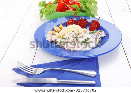 fresh rose wild salmon baked in cream cheese sauce with italian pasta and red hot pepper on blue plate over white wooden table with vegetable salad - stock photo