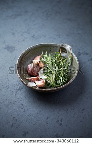 Fresh rosemary and garlic in a ceramic bowl - stock photo