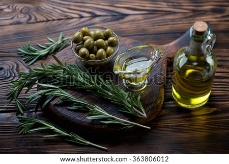 Fresh rosemary, extra virgin olive oil and green olives, close-up