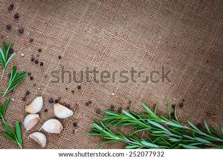 Fresh rosemary, garlic and black pepper on sackcloth background - stock photo