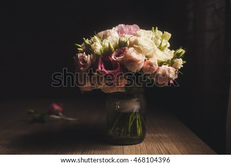 fresh roses in vase with water on a table in the room