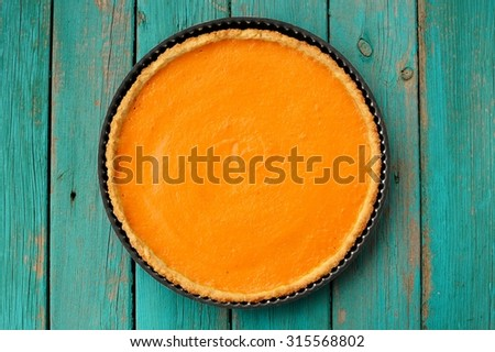 Fresh round bright orange homemade pumpkin pie in baking dish on turquoise table - stock photo