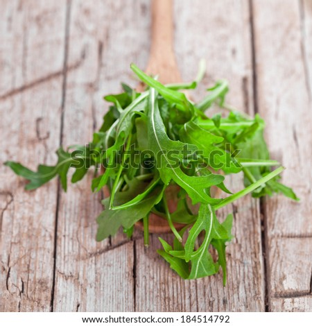 fresh rucola in a spoon on rustic wooden background