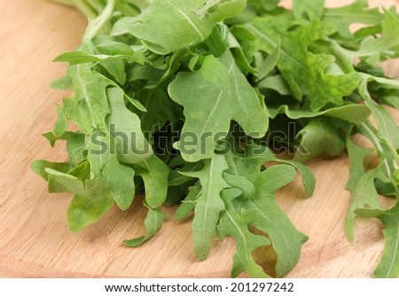 Fresh rucola salad or rocket lettuce leaves on wooden board isolated on white  - stock photo