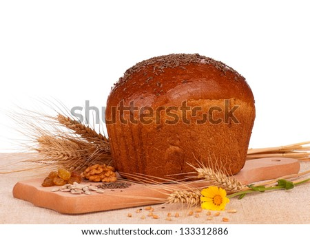 Fresh rye bread on a cutting board on white background - stock photo