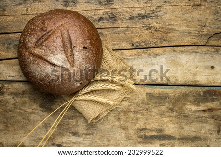 Fresh rye bread with wheat ears on wooden table. Agricultural husbandry background - stock photo