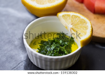 Fresh salad dressing of olive oil, lemon juice and herb parsley in white cup