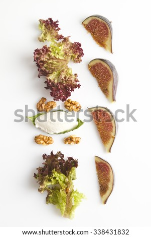 fresh salad healthy salad top view. delicious salad ingredients nut, fig slices and cheese on white background. - stock photo