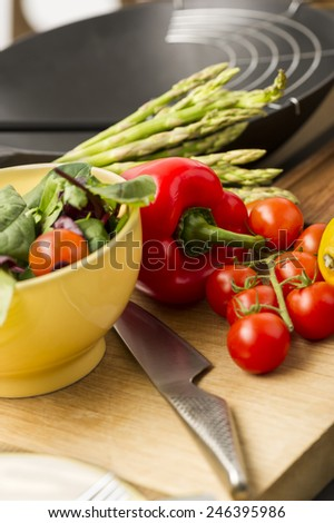 Fresh salad ingredients waiting to be prepared in a kitchen with tomatoes, red bell pepper, leafy herbs and asparagus on a wooden chopping board with a sharp knife - stock photo