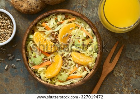 Fresh salad made of savoy cabbage, carrot, celery, and orange with roasted sunflower seeds on top served in wooden bowl, photographed overhead with natural light (Selective Focus, Focus on the salad) - stock photo
