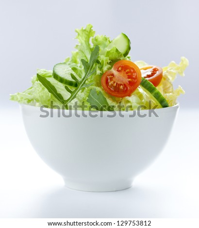 Fresh salad mix with cherry tomatoes, cucumber and rucola in a white bowl