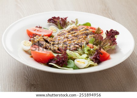 Fresh salad mix with grilled beef, meat cherry tomatoes , boiled quail eggs and  mustard  sauce served on table in white plate - stock photo