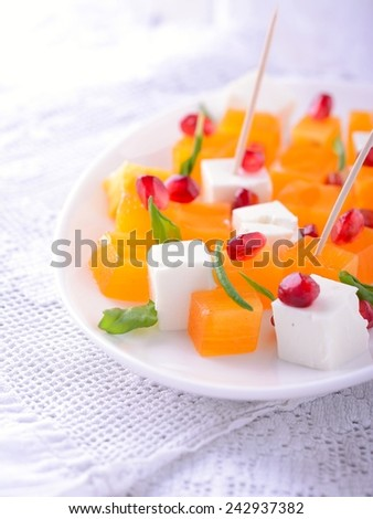 Fresh salad mix with persimmons on wooden table. Selective focus - stock photo