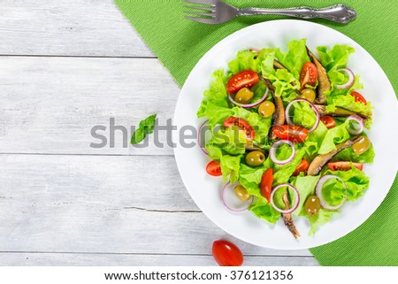 fresh salad of cherry tomatoes, red onion, green olives, lettuce leaves and smoked sprats on a white dish on an old wooden table, horizontal top view - stock photo