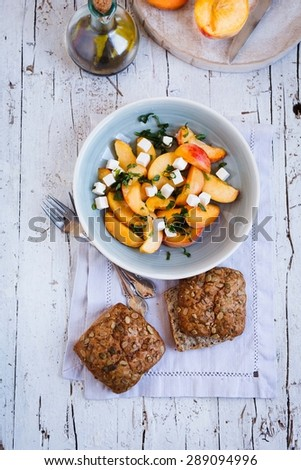 Fresh Salad of peach, leaves of mint and goat cheese with whole burger bread served on rustic white surface from above. Rustic style  - stock photo