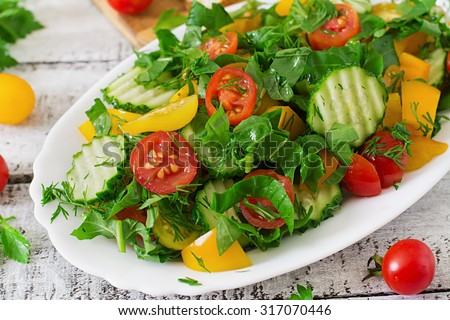 Fresh salad of tomatoes, cucumbers, peppers, arugula and dill - stock photo