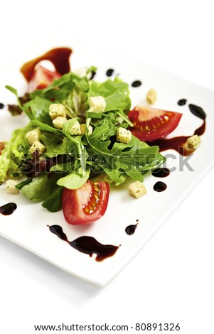 Fresh salad plate garnished with tomatos and balsamic vinegar - stock photo