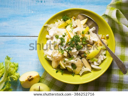 Fresh salad with apples, celery and Chinese cabbage in green plate.