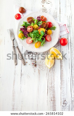Fresh salad with cherry tomatoes, spinach, arugula, romaine and lettuce in a plate on white wooden background - stock photo