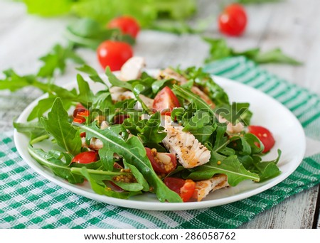Fresh salad with chicken breast, arugula and tomato - stock photo