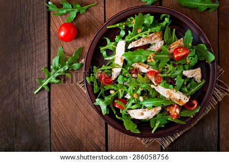 Fresh salad with chicken breast, arugula and tomato. Top view - stock photo