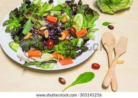 Fresh salad with crab meat on the wooden background