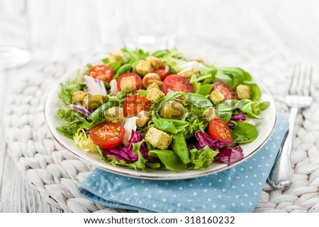 Fresh salad with croutons, tomatoes and olives