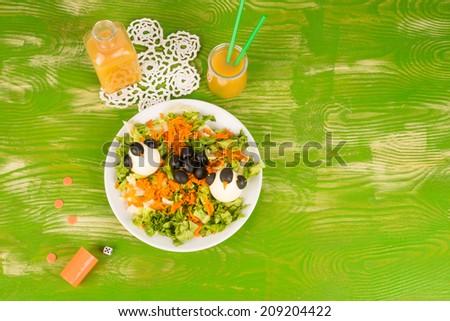 Fresh salad with eggs decorated as penguins, funny kid food - stock photo