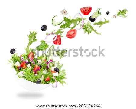 Fresh salad with flying vegetables ingredients isolated on a white background. - stock photo