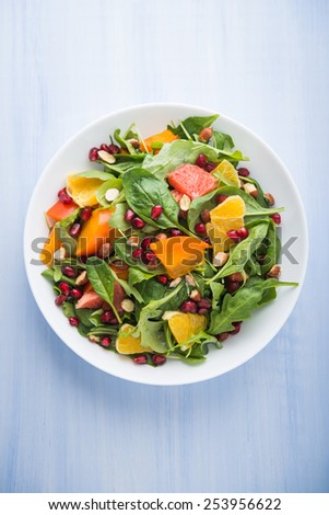 Fresh salad with fruits and greens on blue wooden background top view. Healthy food. - stock photo
