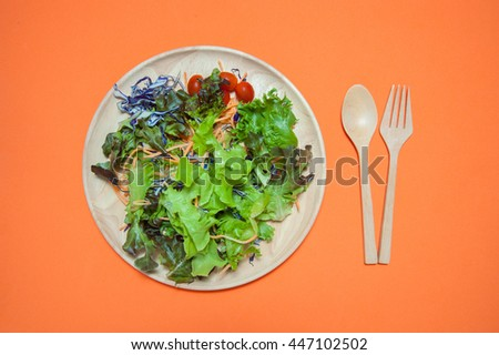 Fresh salad with fruits and greens on orange background top view. Healthy food.eat clean concept. Flat lay.