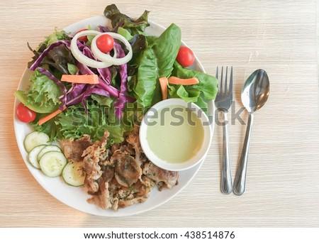 fresh salad with roast pork on white dish and wood background - stock photo
