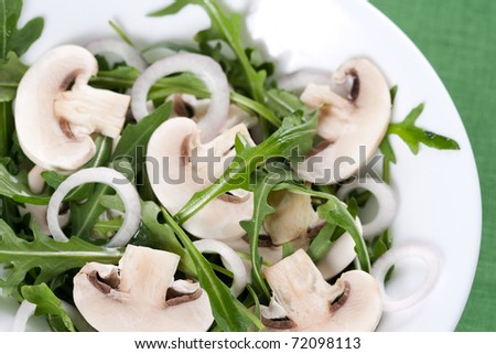 Fresh salad with rucola, mushrooms and onion in bowl - stock photo