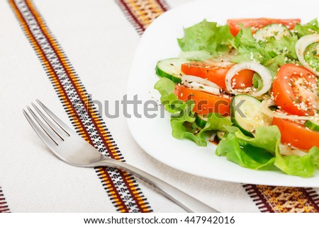 Fresh salad with sliced tomato, cucumber, onion, lettuce seasoned with soy sauce, dry spices and sesame. Low aperture shot, focus on fork and part of salad - stock photo