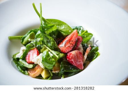 Fresh Salad with strawberries, goat cheese and shrimps dressed with balsamic vinegar and olive oil