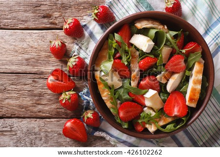 Fresh salad with strawberry, chicken, brie and arugula on the table. horizontal view from above - stock photo