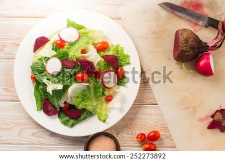 Fresh salad with tomatoes and beetroot, Top view on wood table  - stock photo