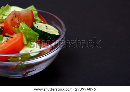 Fresh salad with tomatoes, cucumbers and lettuce. - stock photo