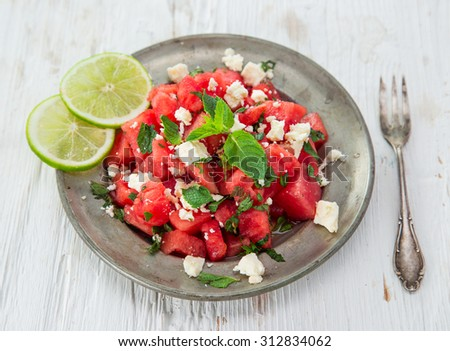 Fresh salad with water-melon, feta cheese, lime and mint. - stock photo